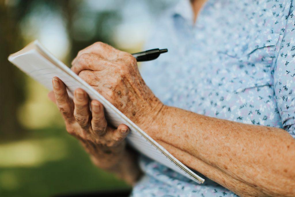 Manos de mujer mayor escribiendo